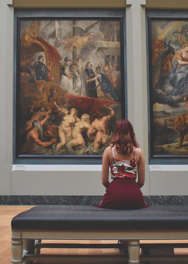 Dame kigger på malerier på museum