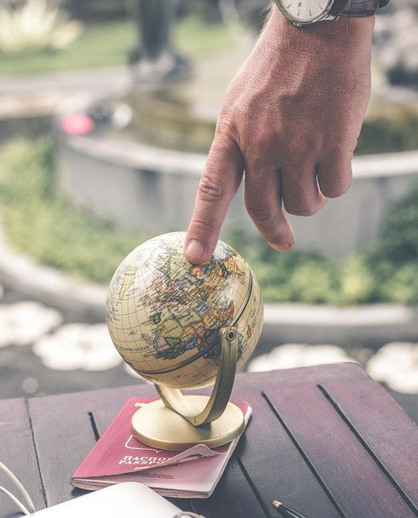 Mand der peger på globus