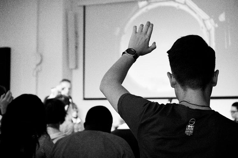 Dreng rækker hånden op ved undervisning.