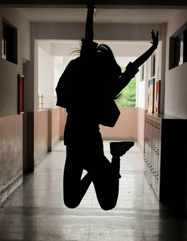 Silhouet af hoppende pige med armene i vejret